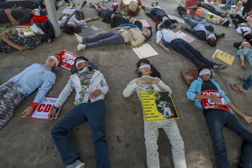 Demonstrators, with eyes blindfolded, lie down in the street to a protest a military coup in Yangon, Myanmar, Tuesday, Feb. 16, 2021. Security forces ...