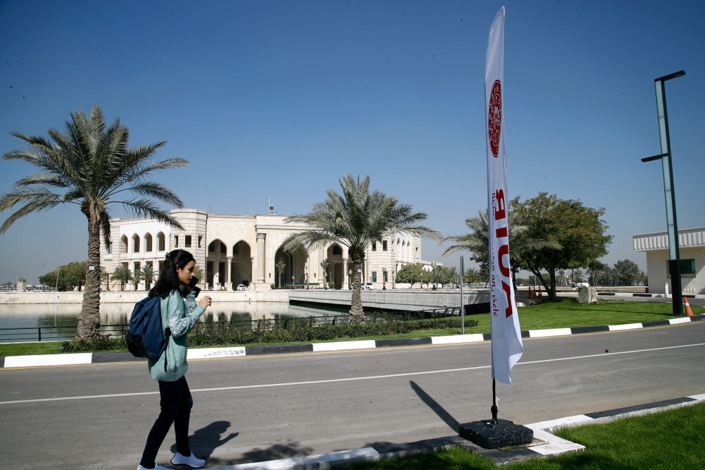 A student walks outside the newly inaugurated American University in Baghdad, Iraq, Monday, Feb. 15, 2021. Encircled by the blue waters of a man-made ...