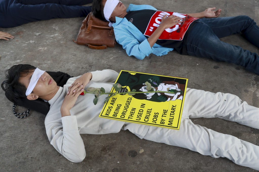 Demonstrators, with eyes blindfolded, lie down in the street to a protest a military coup in Yangon, Myanmar, Tuesday, Feb. 16, 2021.  Security forces...