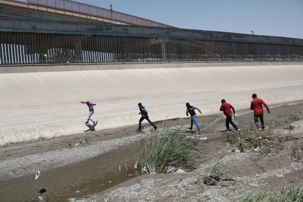 FILE - In this June 15, 2019, file photo, migrants cross the Rio Bravo illegally to surrender to the American authorities, on the U.S.-Mexico border b...
