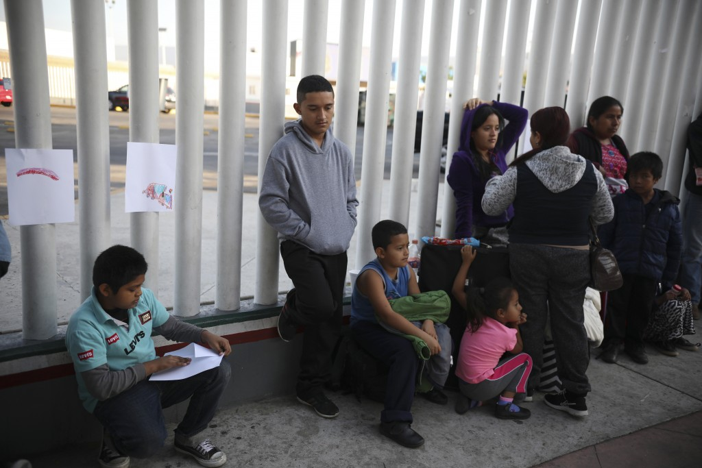 FILE - In this Sept. 13, 2019, file photo, Central American migrants wait to see if their number will be called to cross the border and apply for asyl...