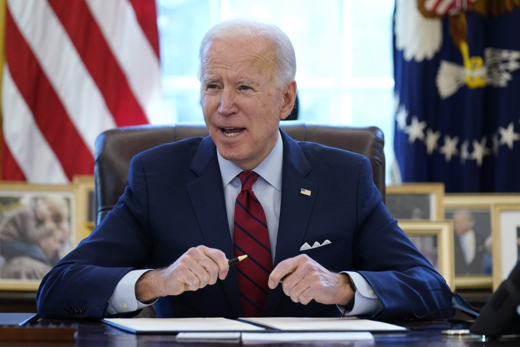 FILE - In this Jan. 28, 2021 file photo, President Joe Biden signs a series of executive orders in the Oval Office of the White House in Washington. B...