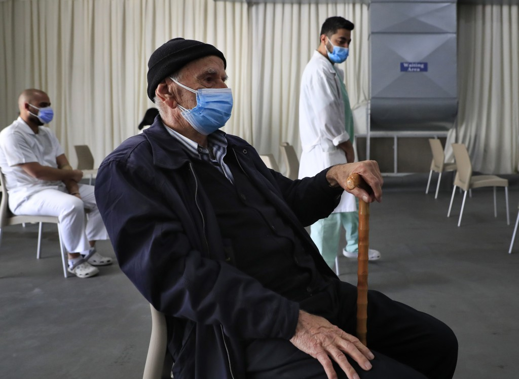A man waits his turn to receive the Pfizer-BioNTech COVID-19 vaccine during a nationwide vaccination campaign, at the Saint George Hospital, in Beirut...