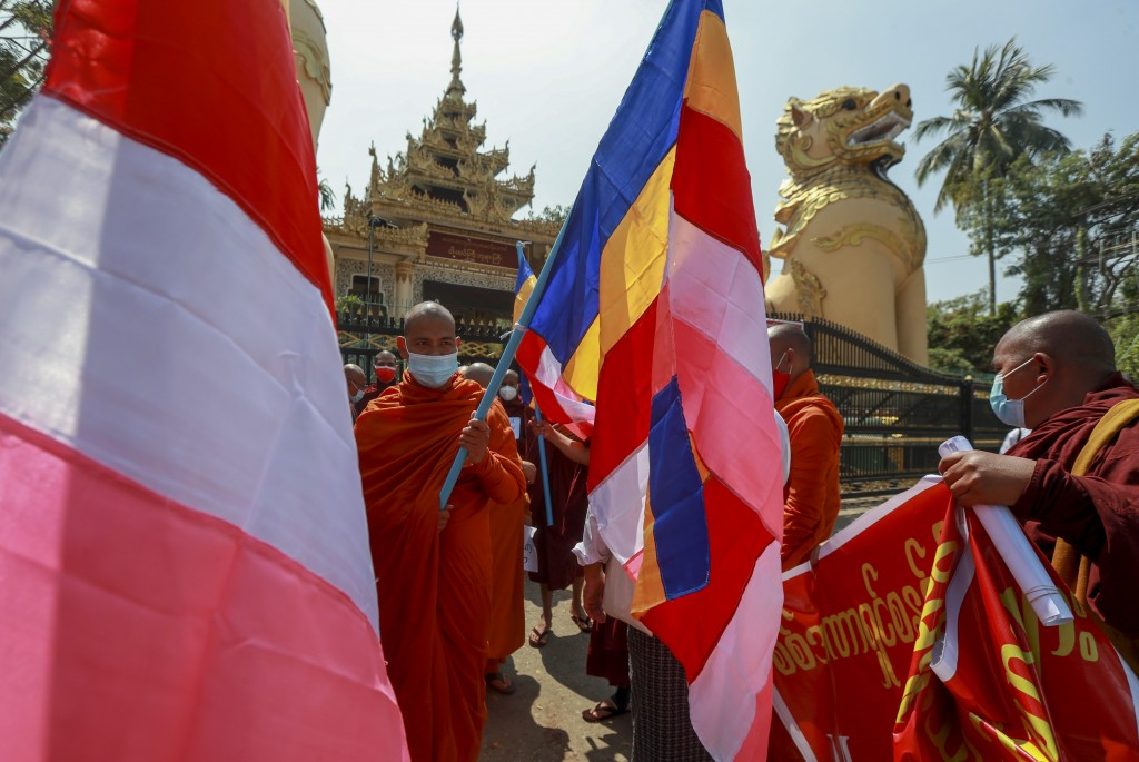Buddhist monks holding Buddhist flags prepare to march against the military coup in Yangon, Myanmar Tuesday, Feb. 16, 2021. Police in Myanmar have fil...