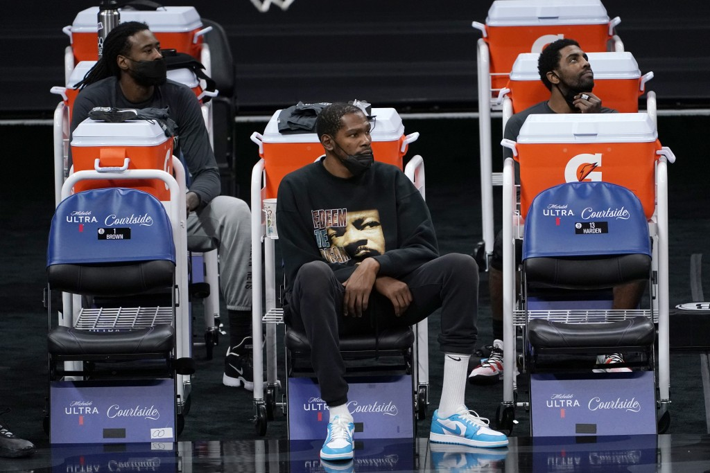 Brooklyn Nets DeAndre Jordan, left, Kevin Durant, center, and Kyrie Irving watch their teammates play the Sacramento King during the second half of an...