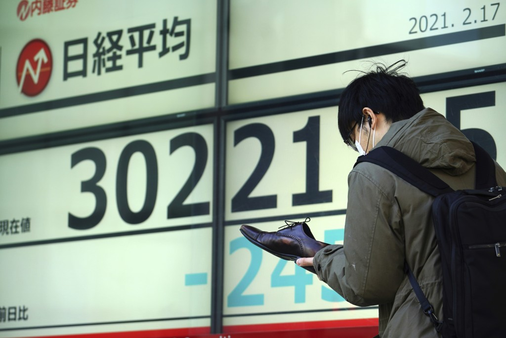A man wearing a protective mask checks his shoe in front of an electronic stock board showing Japan's Nikkei 225 index at a securities firm Wednesday,...