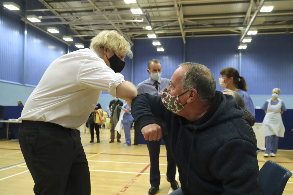 Britain's Prime Minister Boris Johnson greets a person as they wait to receive an Oxford AstraZeneca COVID-19 vaccine at a vaccination centre in Cwmbr...