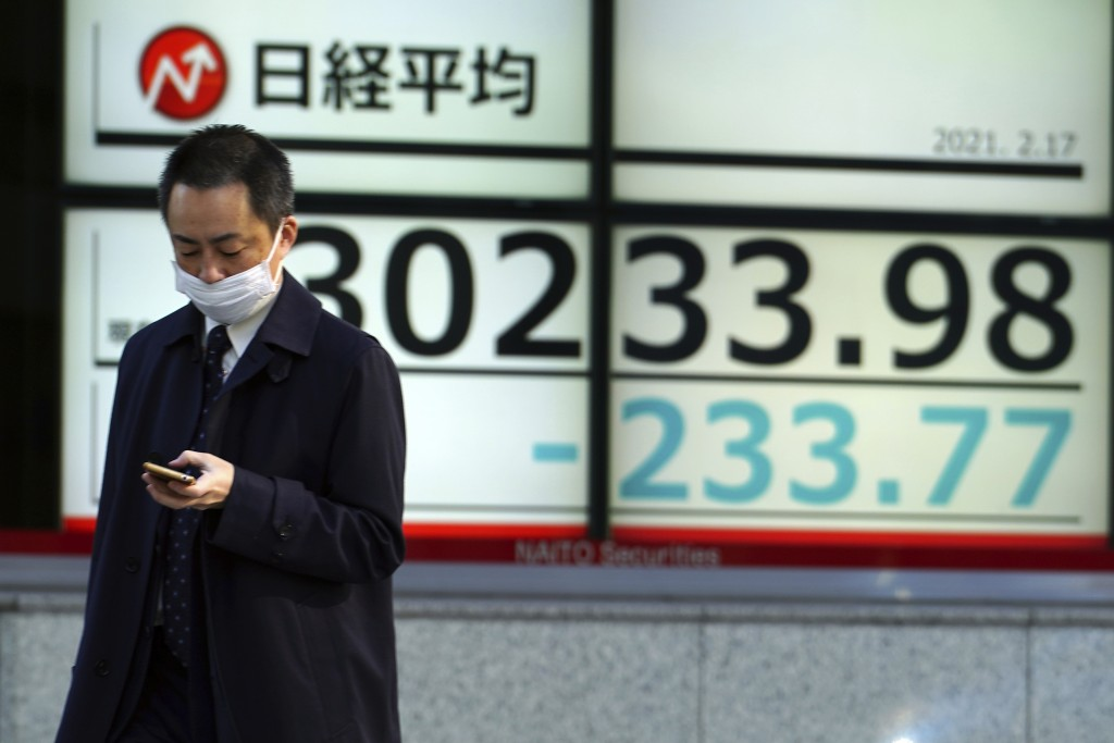 A man wearing a protective mask walks in front of an electronic stock board showing Japan's Nikkei 225 index at a securities firm Wednesday, Feb. 17, ...