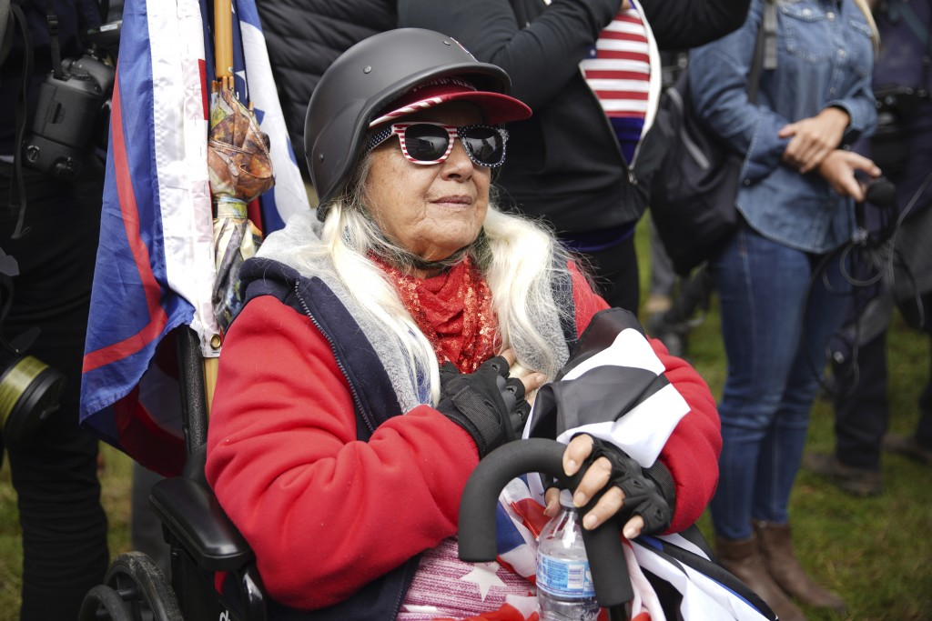 FILE - In this Sept. 26, 2020, file photo, a woman does the Pledge of Allegiance as members of the Proud Boys and other right-wing demonstrators rally...