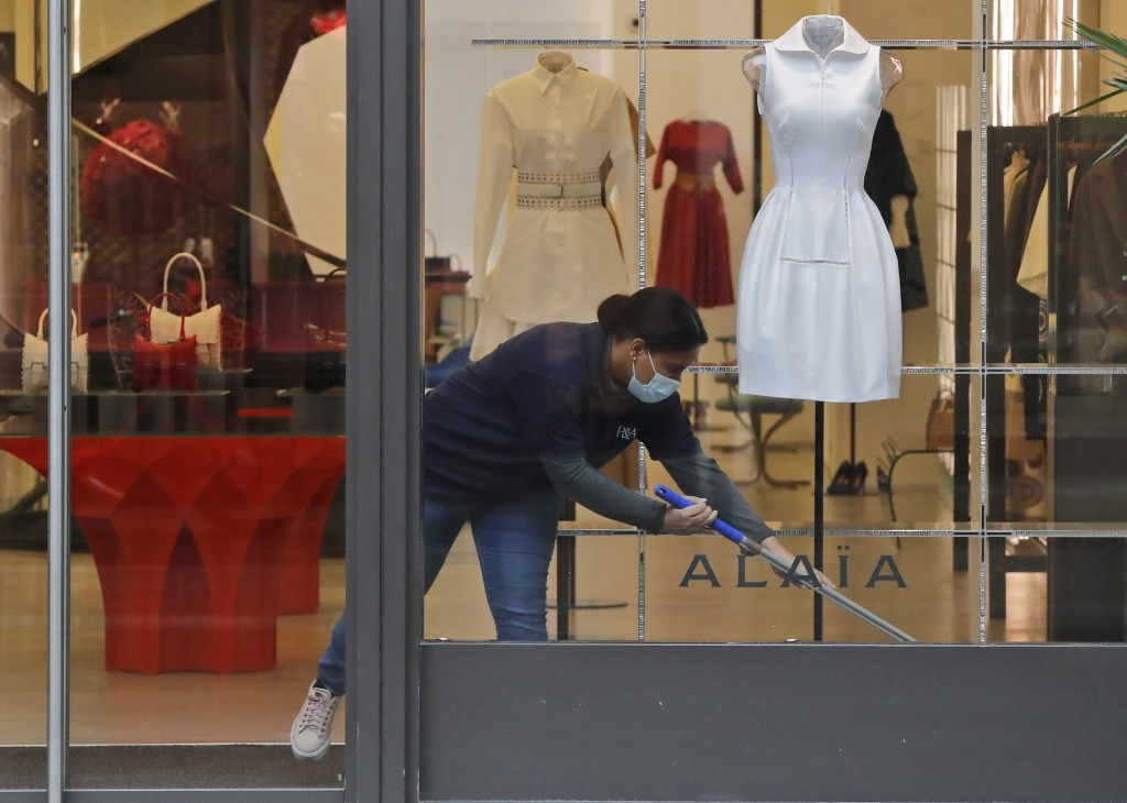 A woman wearing a face covering due to the COVID-19 pandemic cleans inside a shop during lockdown in London, Wednesday, Feb. 17, 2021. (AP Photo/Frank...