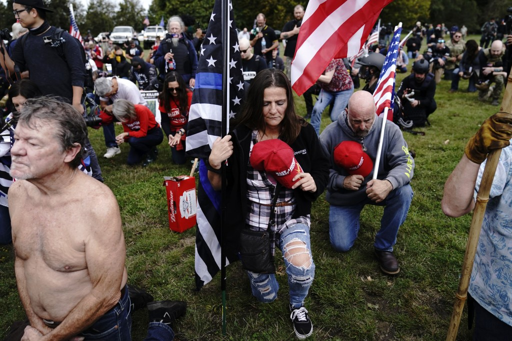 FILE - In this Sept. 26, 2020, file photo, members of the Proud Boys and other right-wing demonstrators kneel in prayer at a rally, in Portland, Ore. ...