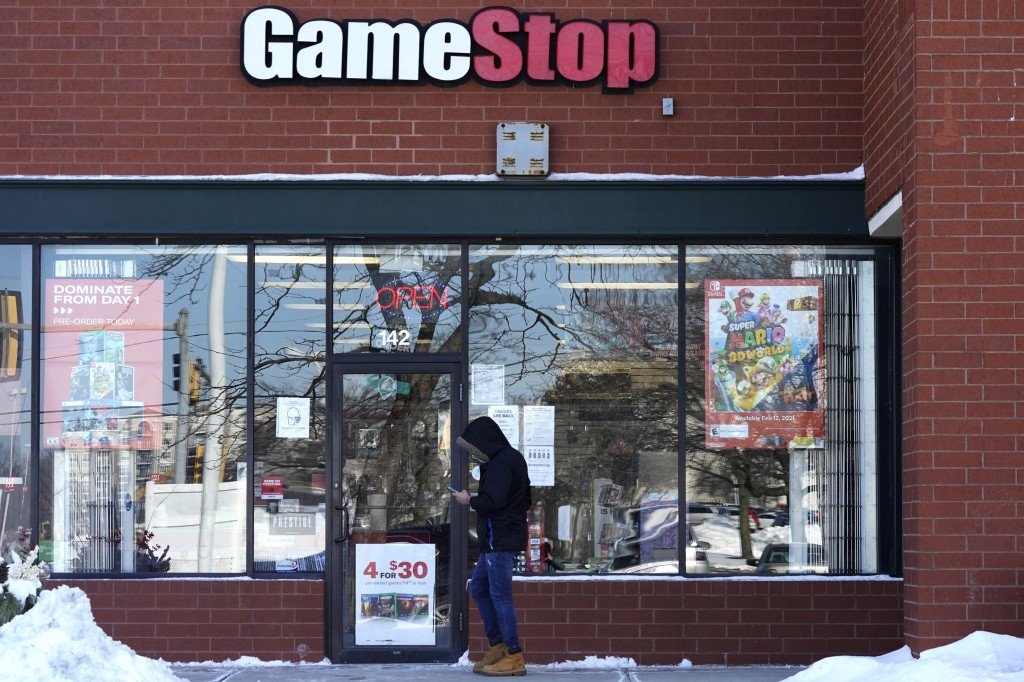 FILE - In this Jan. 28, 2021 file photo, a customer checks on his cellphone as he walks to a GameStop store in Vernon Hills, Ill. The frenzy around Ga...