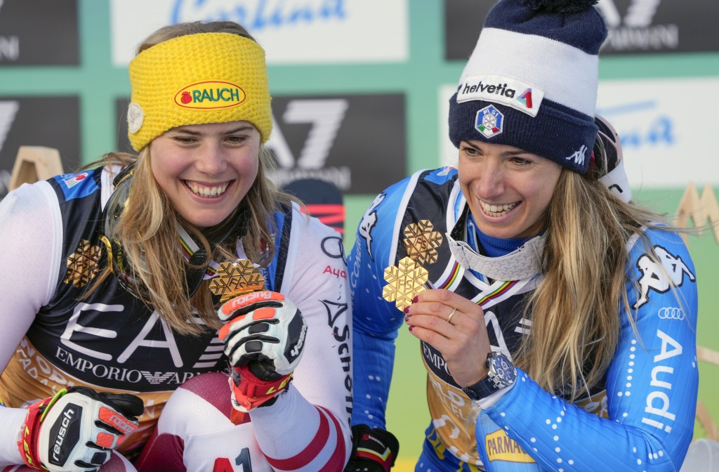 Italy's Marta Bassino, right, and Austria's Katharina Liensberger show their gold medals after the parallel giant slalom, at the alpine ski World Cham...