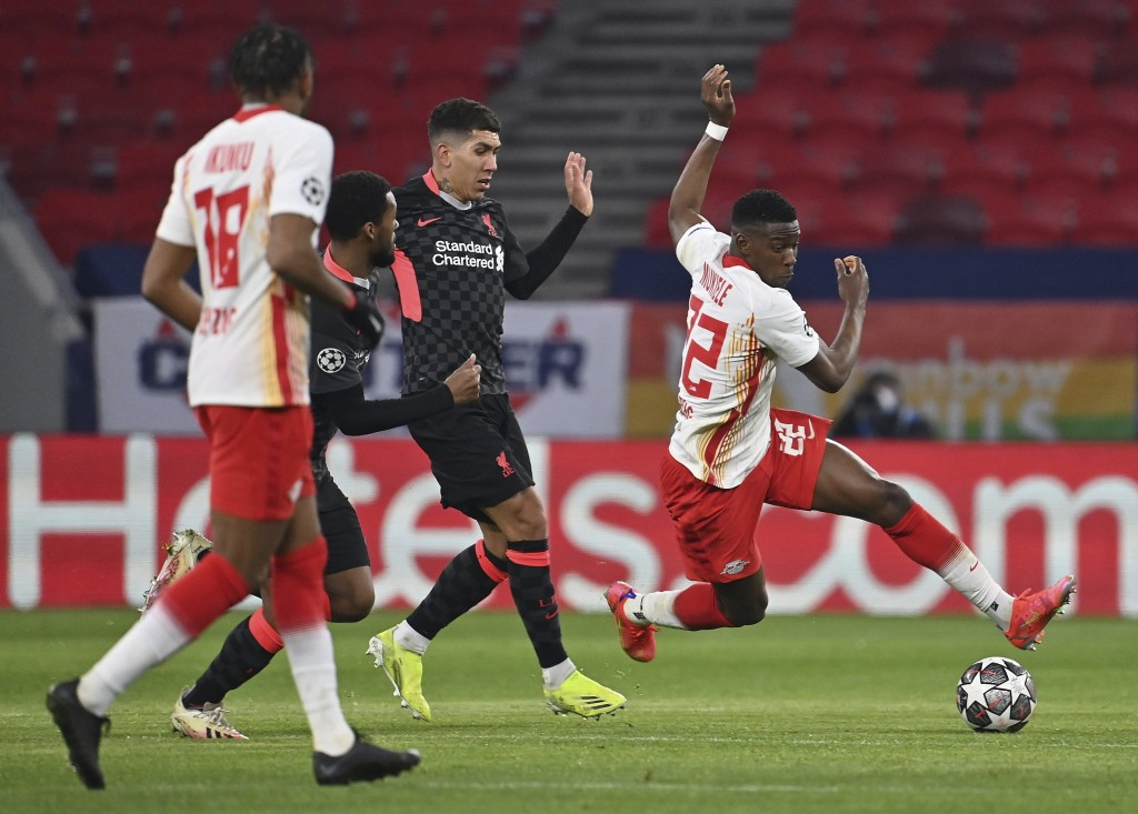 RB Leipzig's Nordi Mukiele, right, tries to get past Liverpool's Roberto Firmino, center, during the Champions League round of 16, first leg, soccer m...
