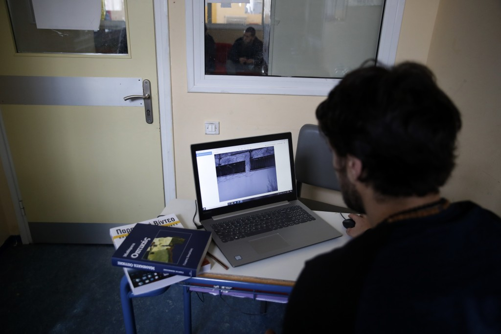 An inmate checks a photo before taking online exams for his university exams photography and audiovisual arts course, at Avlona's prison school, north...