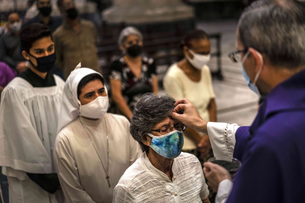 Wearing a mask against the spread of the new coronavirus, a woman has her forehead marked with ash during Ash Wednesday in Havana, Cuba, Wednesday, Fe...