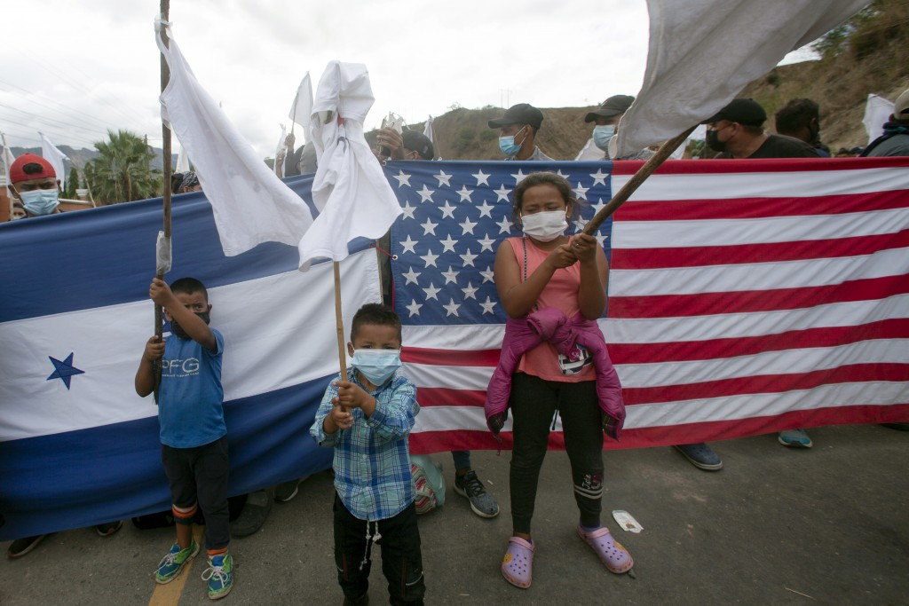 Honduran migrant children raise white flags in front of a Honduran and American flag, as they are blocked by Guatemalan soldiers and police from advan...