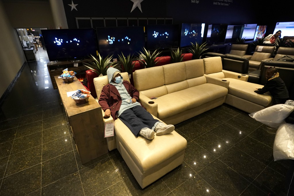 Jenesis Heath rests inside a Gallery Furniture store which opened as a shelter Wednesday, Feb. 17, 2021, in Houston. Millions in Texas still had no po...