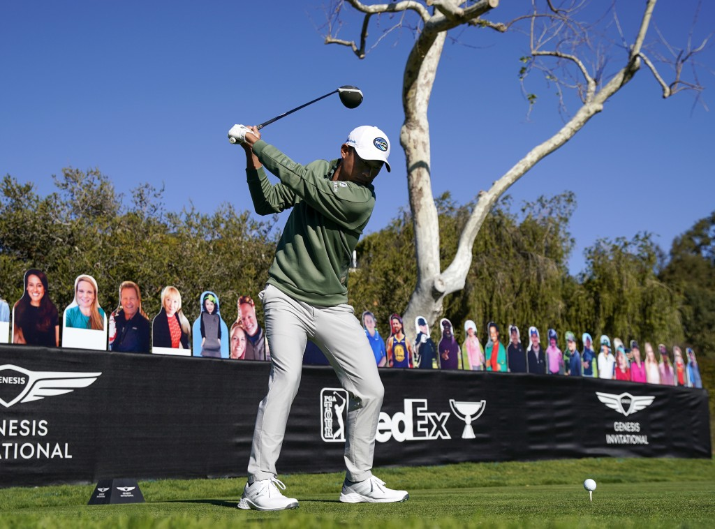 Collin Morikawa tees off on the 18th hole in front of cardboard cutout fans during the Genesis Invitational pro-am golf event at Riviera Country Club,...