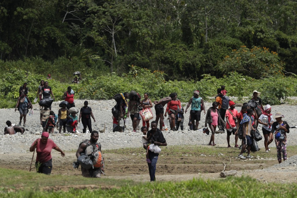 Migrants cross the Tuquesa River after a trip on foot through the jungle to Bajo Chiquito, Darien province, Panama, Wednesday, Feb. 10, 2021. Panama r...