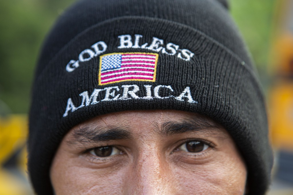 An Honduran migrant who tried to the U.S.-Mexico border eyes the camera wearing a God Bless America beanie, after he was detained and returned to his ...