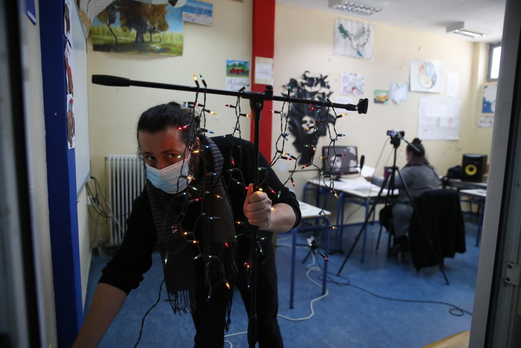 "Music teacher, Nikos Karadosidis, uses Christmas lights as a makeshift ""recording"" light, warning those outside the classroom to be quiet during recor..."