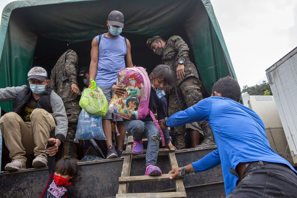 A Honduran migrant child is helped off a Guatemalan army truck after being returned to El Florido, Guatemala, one of the border points between Guatema...