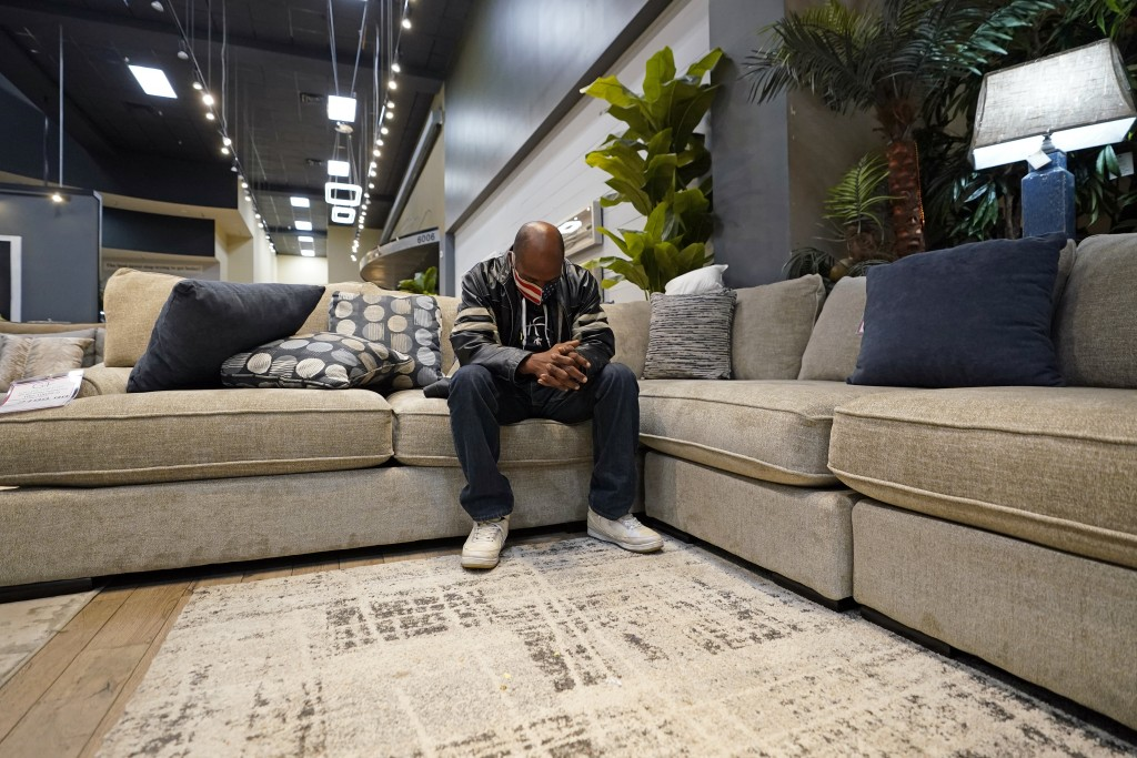 Charvis Johnson sits on a couch inside a Gallery Furniture store which opened as a shelter Wednesday, Feb. 17, 2021, in Houston. Millions in Texas sti...