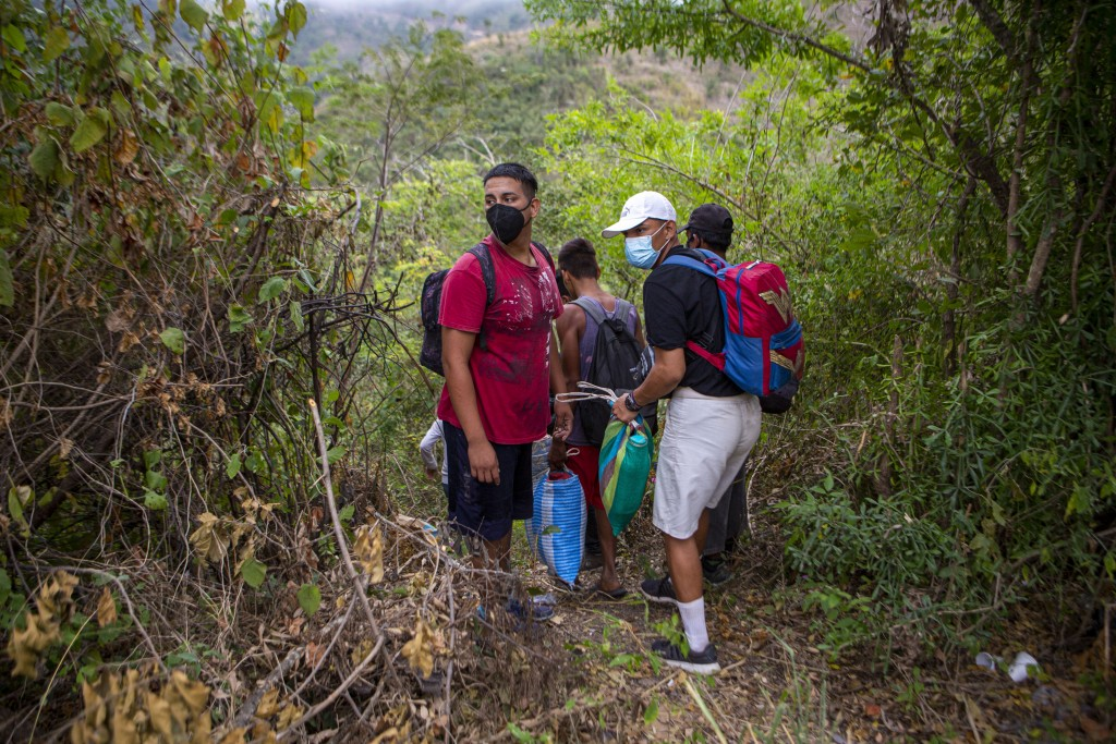 Honduran migrants observe a police checkpoint as they take an alternative route to avoid being detained in Chiquimula, Guatemala, Tuesday, Jan. 19, 20...