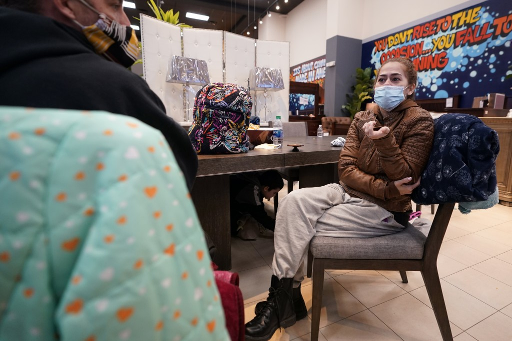 Tina Rios, right, and her husband, Eric Bennis, talk about losing power at their home while sitting inside a Gallery Furniture store which opened as a...