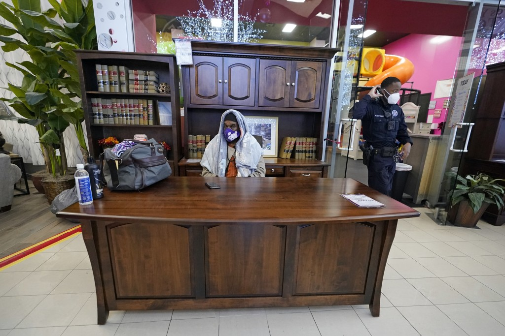 Michael Singletary rests behind a desk at a Gallery Furniture store which opened as a shelter for those without power Wednesday, Feb. 17, 2021, in Hou...