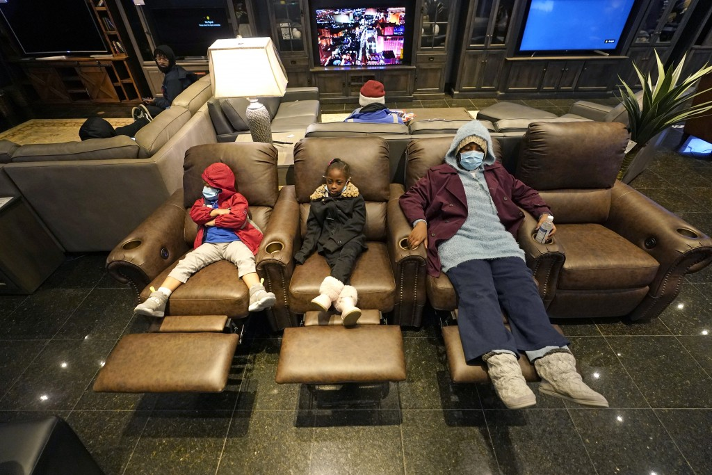 Joecyah Heath, left, Morning Day, center, and Jenesis Heath rest in recliners at a Gallery Furniture store which opened as a shelter Wednesday, Feb. 1...