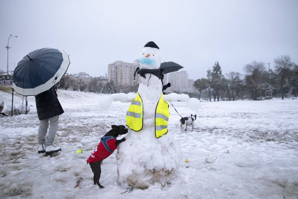 People walk their dogs next to a snowman decorated with a face mask in a snow-covered park, in Jerusalem, Thursday, Feb. 18, 2021. (AP Photo/Oded Bali...