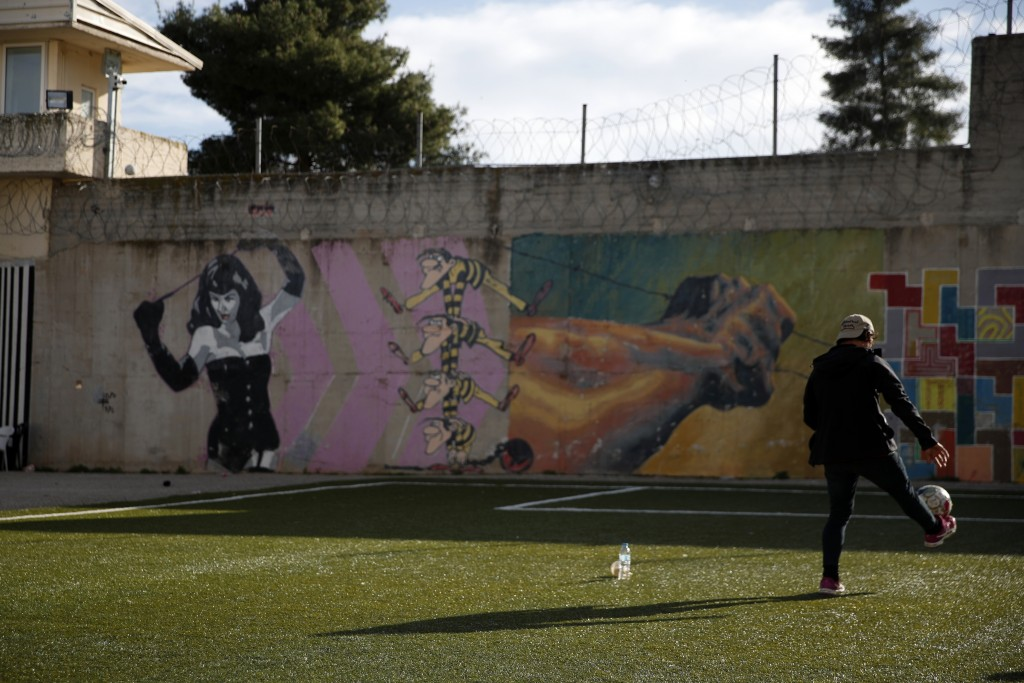 An inmate plays with a ball at the yard of Avlona prison, north of Athens, Wednesday, Feb. 10, 2021. With Greece's schools shut due to the pandemic, a...