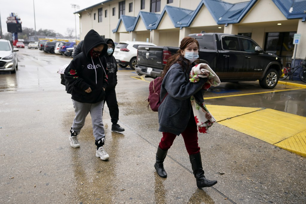A family arrives at a Gallery Furniture store which opened as a shelter Wednesday, Feb. 17, 2021, in Houston. Millions in Texas still had no power aft...