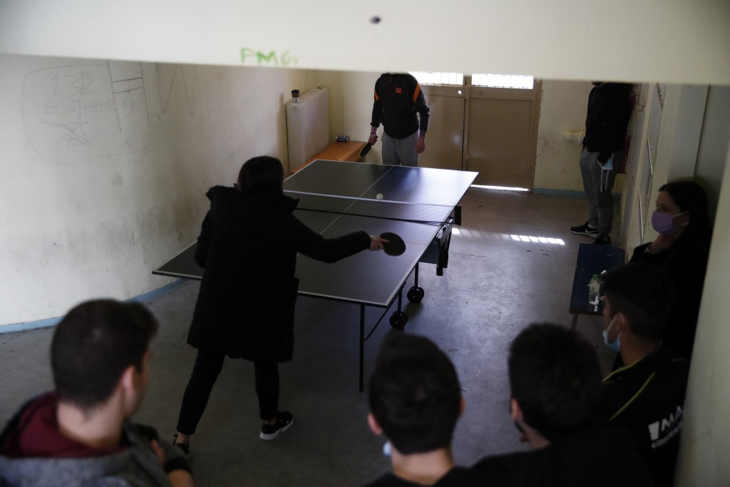 A teacher plays table tennis with an inmate as others watch them at Avlona's prison school, north of Athens, Wednesday, Feb. 10, 2021. With Greece's s...