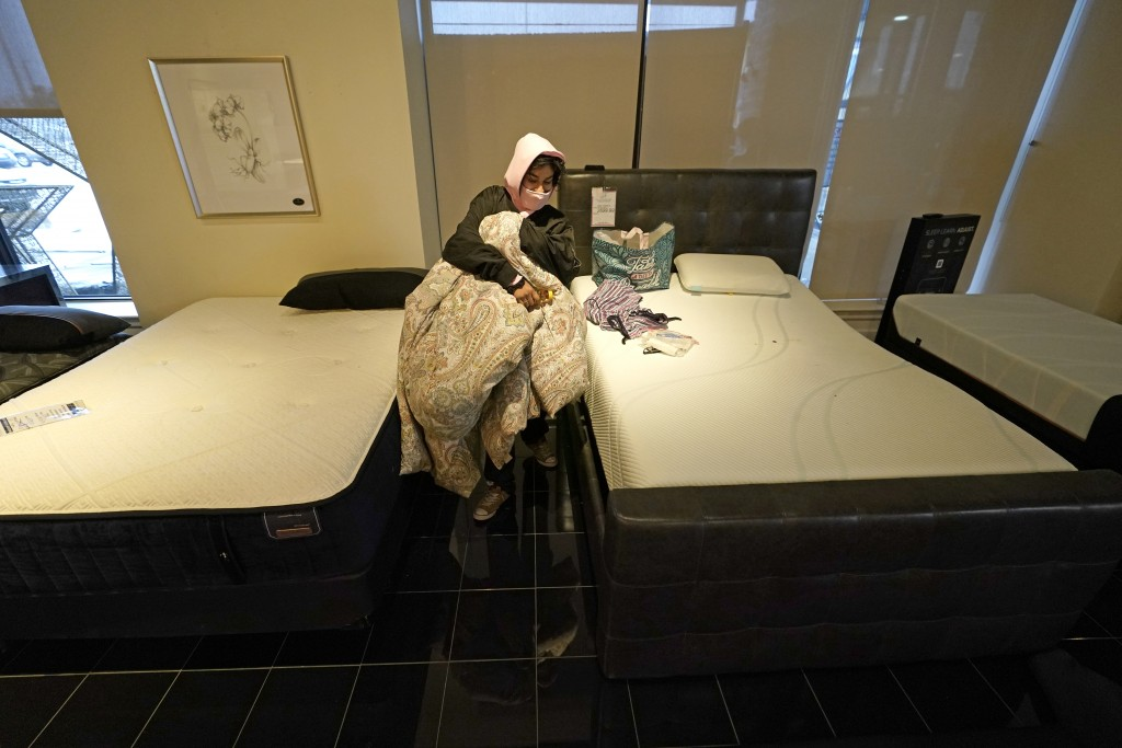 Dialina Gonzalez gathers her belongings after spending the night on a mattress inside a Gallery Furniture store which opened as a shelter Wednesday, F...