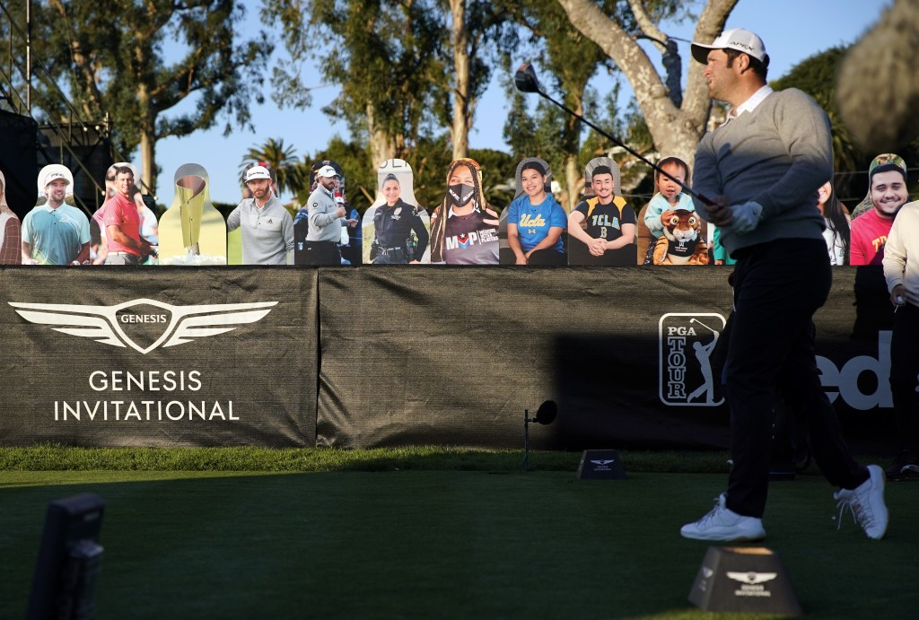 Jon Rahm tees off on the 10th hole in front of cardboard cutout fans during the first round of the Genesis Invitational golf tournament at Riviera Cou...