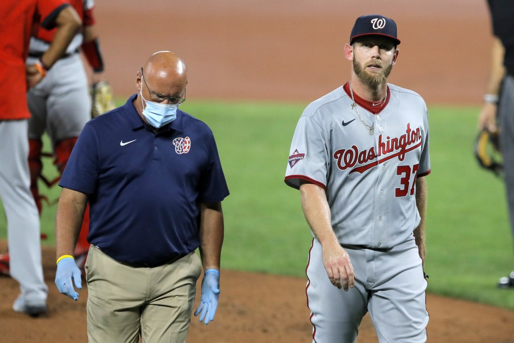 FILE - Washington Nationals starting pitcher Stephen Strasburg, right, walks with a member of the training staff as he heads to the dugout after leavi...