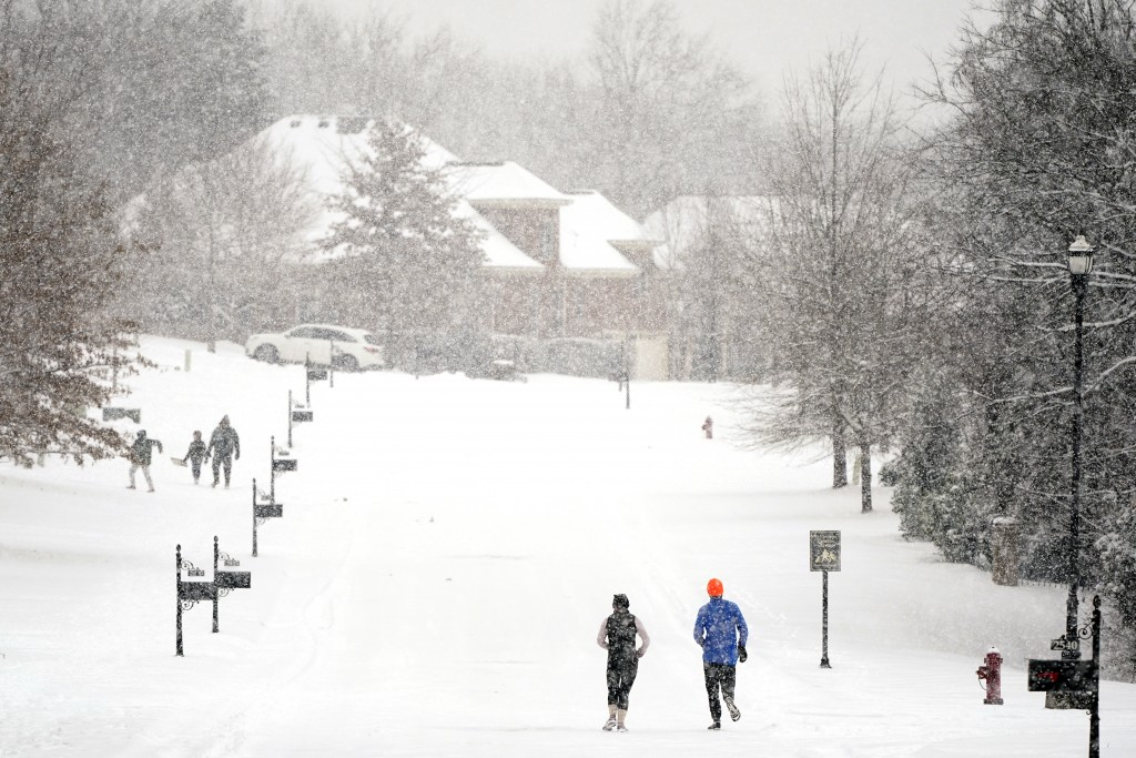 Joggers run down a street empty of cars Thursday, Feb. 18, 2021, in Nolensville, Tenn. A second winter storm in a week is bringing more snow to much o...