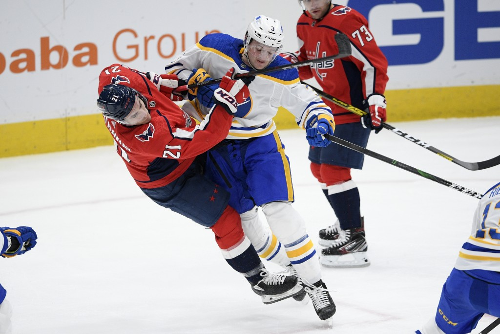 Buffalo Sabres defenseman William Borgen (3) shoves Washington Capitals right wing Garnet Hathaway (21) during the second period of an NHL hockey game...