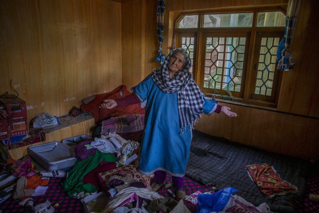 A Kashmiri woman stands amid belongings in a house allegedly ransacked by security forces after suspected militants killed a policeman in Beerwah area...
