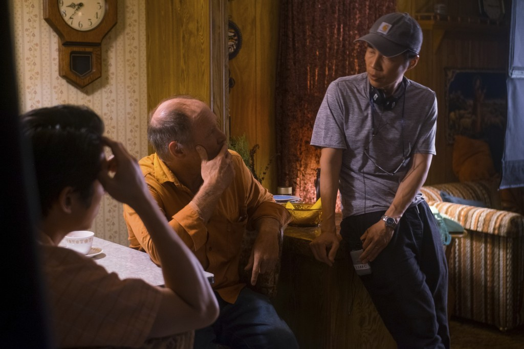 """This image released by A24 shows Steven Yeun, left, and Will Patton, center, with Lee Isaac Chung on the set of """"Minari.""""  (Joe Rushmore/A24 via AP)"""