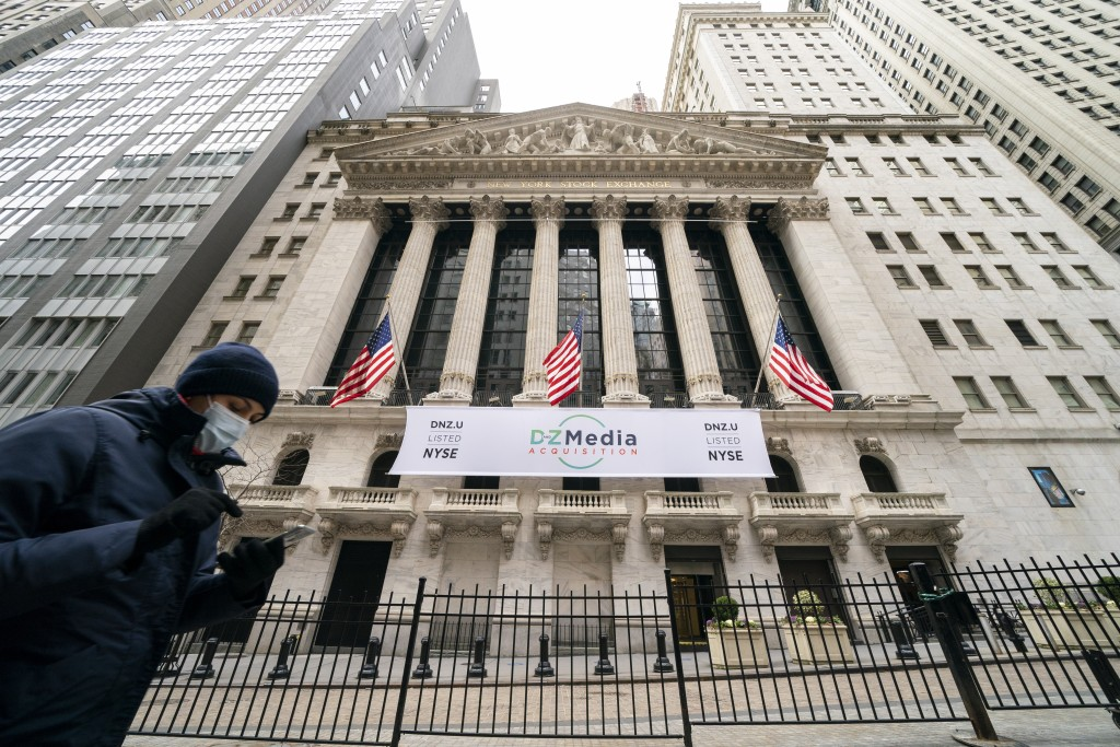 FILE - Pedestrians pass the New York Stock Exchange, Wednesday, Jan. 27, 2021, in New York.  Stocks are opening higher on Wall Street following three ...