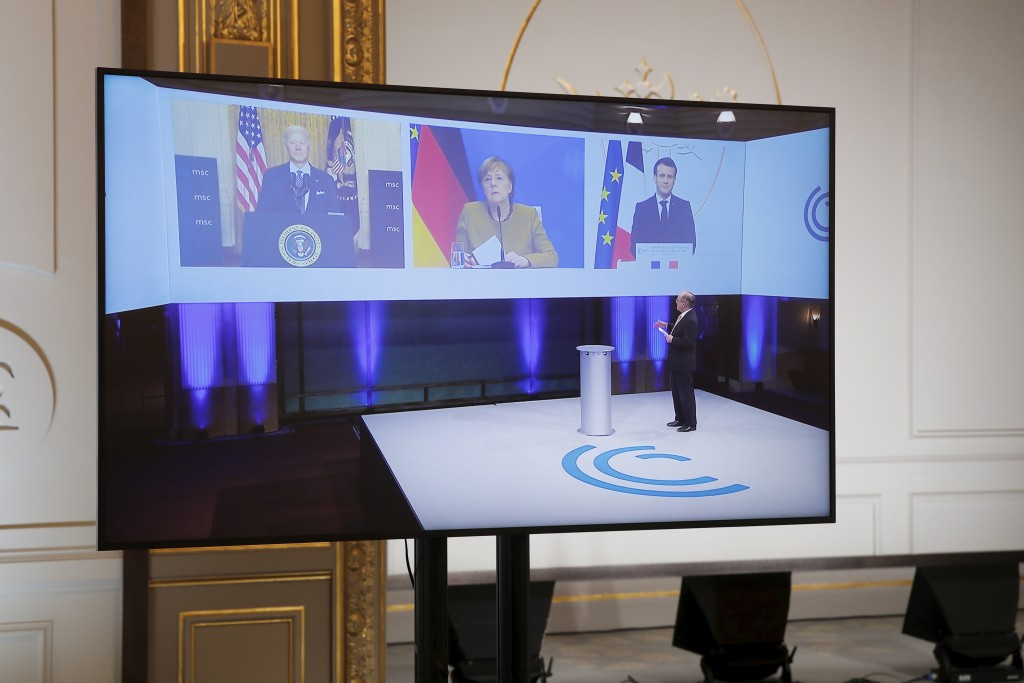 French President Emmanuel Macron, right on screen, attends a video-conference meeting with U.S. President Joe Biden and German Chancellor Angela Merke...