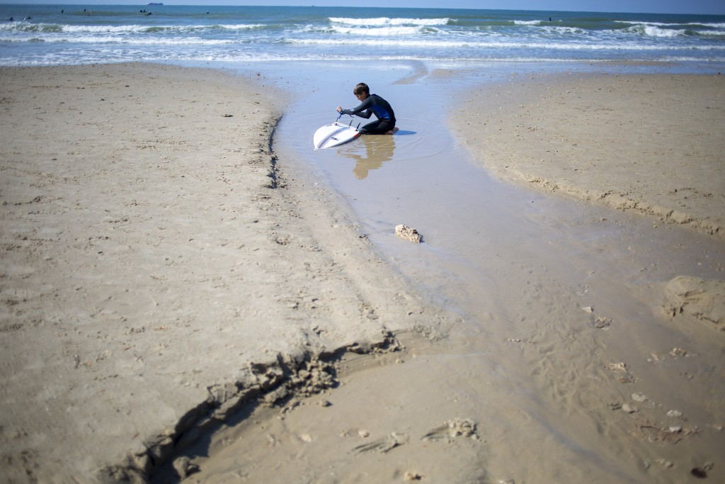 A surfer cleans his tar covered surfboard from an oil spill in the Mediterranean Sea in Gador nature reserve near Hadera, Israel, Saturday, Feb. 20, 2...