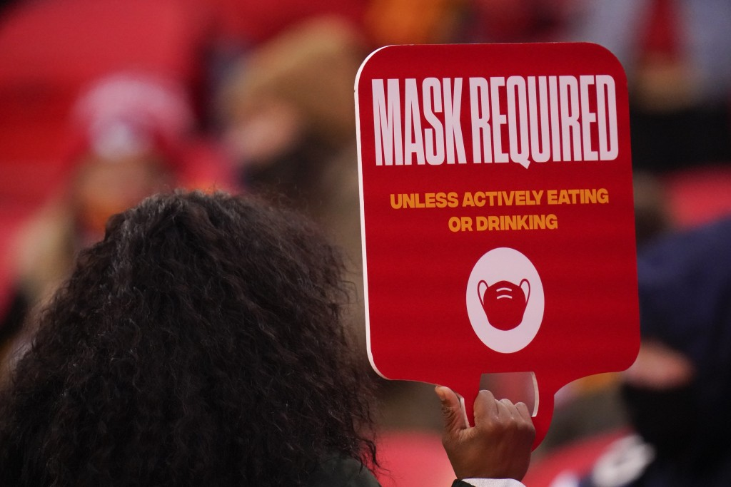 FILE - In this Jan. 3, 2021, file photo, an Arrowhead Stadium usher holds a mask required sign during the first half of an NFL football game in Kansas...