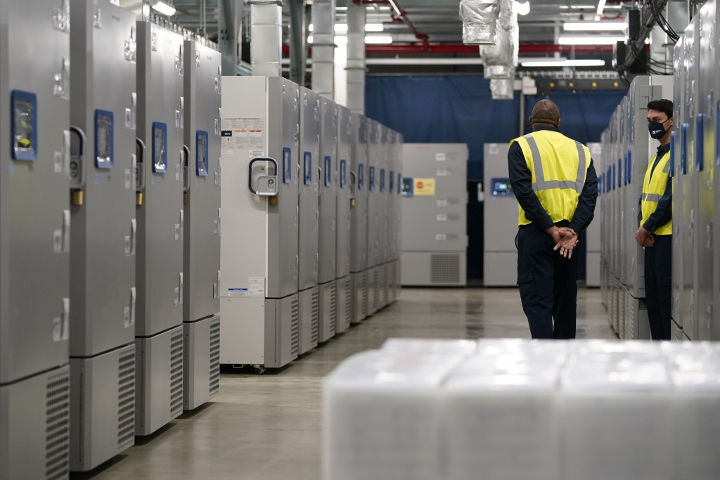People stand near freezers used to store Pfizer-BioNtech's COVID-19 vaccine at a Pfizer manufacturing site, Friday, Feb. 19, 2021, in Portage, Mich. E...