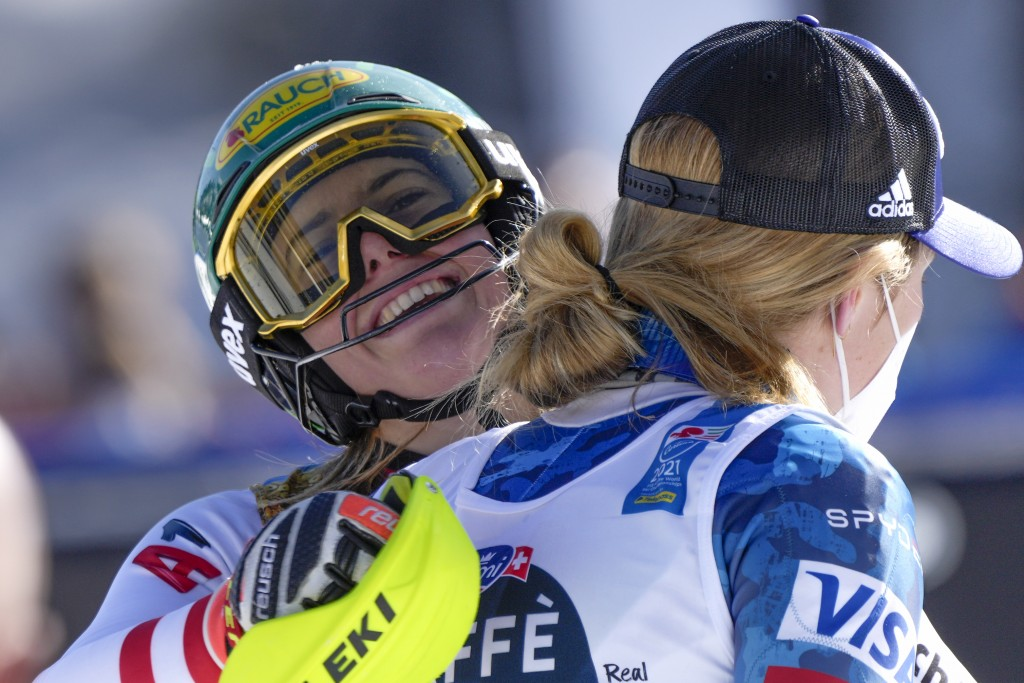 Austria's Katharina Liensberger, face to camera, winner of the women's slalom, celebrates with third placed United States' Mikaela Shiffrin, at the al...