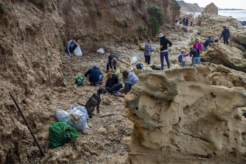 People clean tar from an oil spill in the Mediterranean sea in Gador nature reserve near Hadera, Israel, Saturday, Feb. 20, 2021. Hundreds of voluntee...